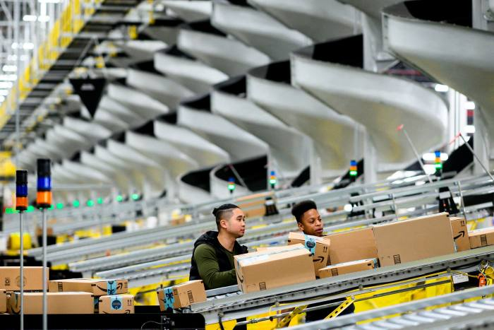 Amazon employees work at a distribution station in New York. Federal investigators have also opened probes into both Amazon and Apple