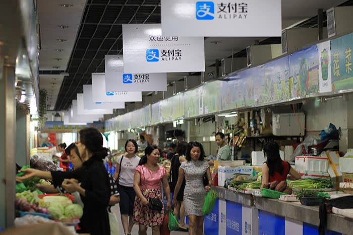 Shoppers in a food market in Wenzhou, China, with signs to say Alipay is accepted