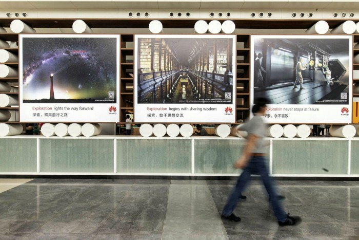 Employees walk past advertisements near the canteen at the Huawei headquarters in Shenzhen, China