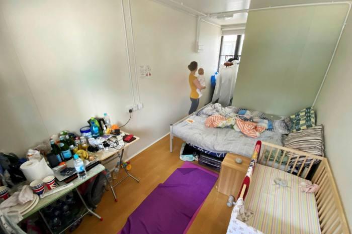 Une femme tient un enfant dans une pièce du centre d'isolement de Penny's Bay sur l'île de Lantau à Hong Kong