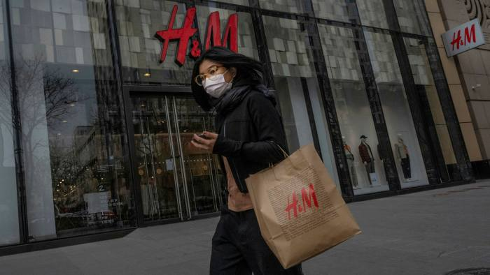A woman with an H&M shopping bag walks outside an H&M store in Beijing