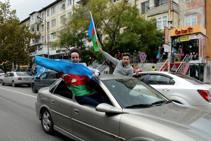 People wave national flags from a car in Azerbaijan's capital Baku as they celebrate the fall of Shusha to Azeri forces