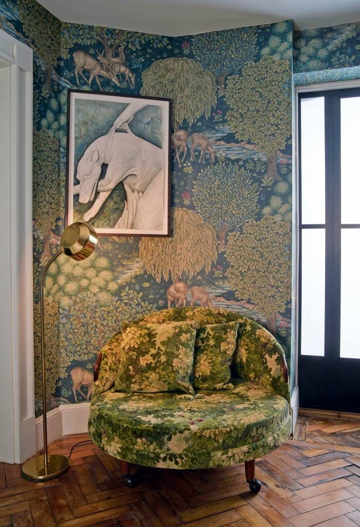 A love seatcovered with verdure tapestry in a Bloomsbury home designed by Rachel Chudley