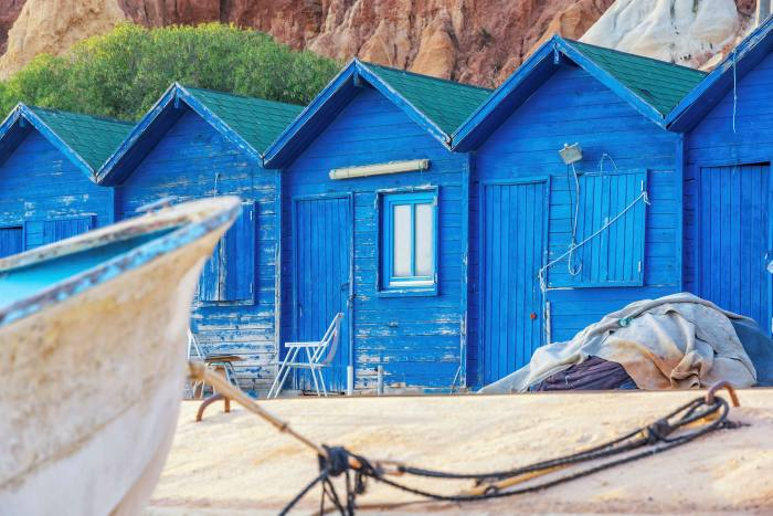 Cabanas de pescador azuis na praia de Olhos d'Água