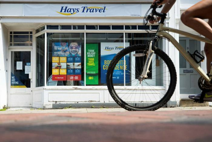A cyclist passes a Hays Travel shop in Canterbury, UK