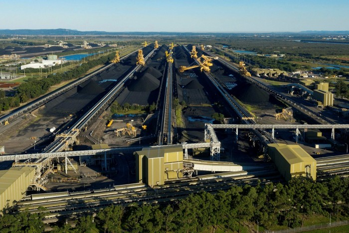 Stacker-reclaimers operate next to stockpiles of coal at the Newcastle Coal Terminal in March after Australia's recent one-in-100 year flooding event