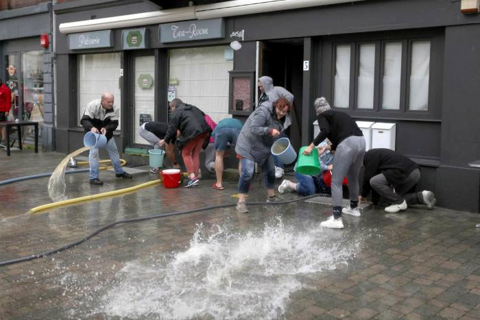 People fetch water on a flooded street in Spa, Belgium