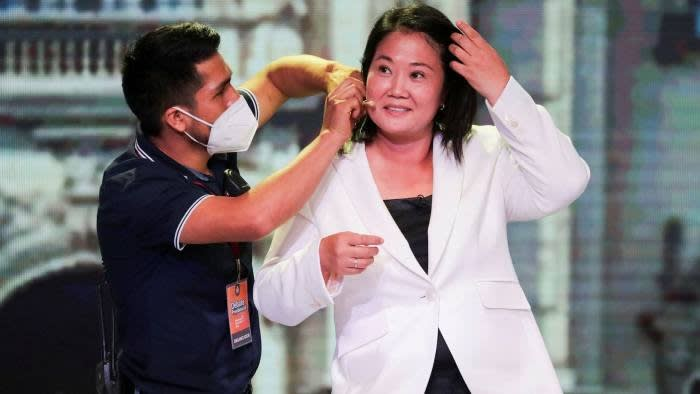 Presidential candidate Keiko Fujimori of the Fuerza Popular party in Peru has her microphone adjusted as she prepares to participate in a presidential debate last month