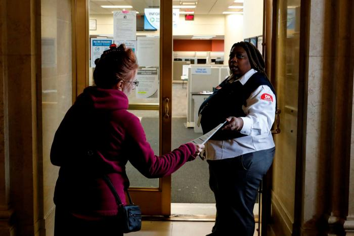 A security guard hands a leaflet to a woman  outside the State of Michigan Unemployment Agency office in Detroit. The city's unemployment rate is estimated to be 48%