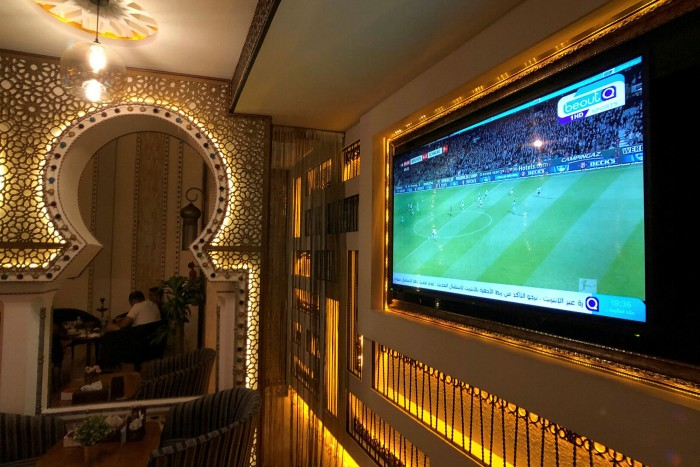 A screen in a Saudi Arabian cafe shows a beoutQ broadcast. The Arabic-language pirate network emerged after Saudi Arabia cut diplomatic ties with Qatar