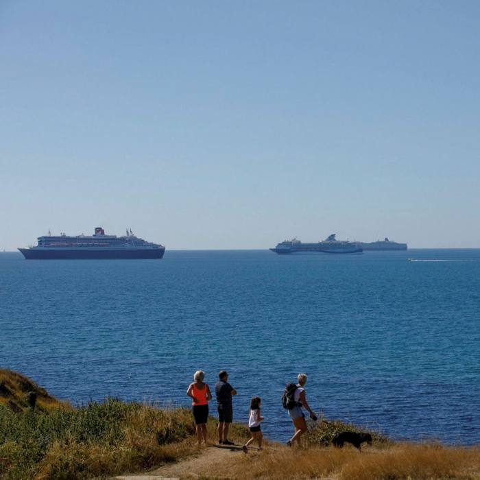 A coastal footpath off Weymouth in England, in view of cruise ships operated by companies including Tui