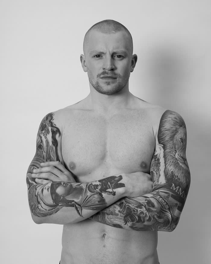Portrait of a bare-chested Adam Peaty. His heavily tattooed arms are folded