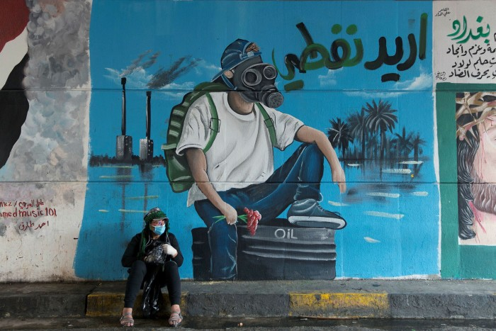 A protester sits in front of a mural that reads, 'I want my oil', in Baghdad. If Iraq — which has 145bn barrels of proven crude reserves — stays dependent on oil, its finance minister says, 'it could be catastrophic'