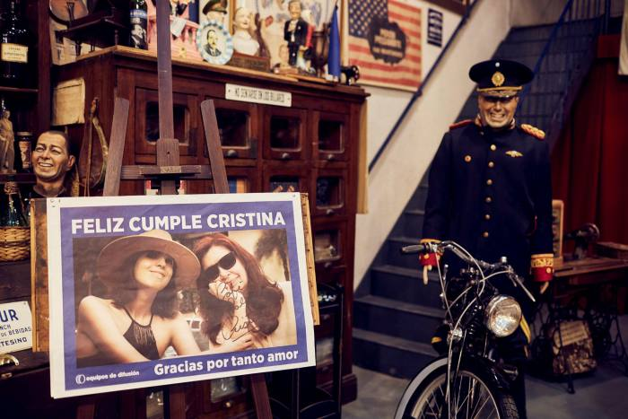 A poster showing Cristina Fernández de Kirchner with her daughter Florencia at the vice-president's birthday party, held at Las Palabras; beside it is a figure of Juan Perón