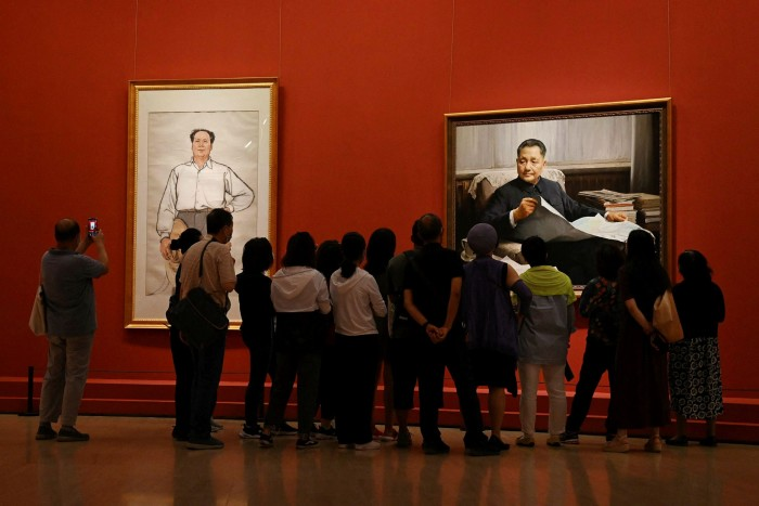 Visitors look at a paintings of  Mao Zedong (L) and Deng Xiaoping at an exhibition of art celebrating the 100th anniversary of the founding of the Communist party in Beijing