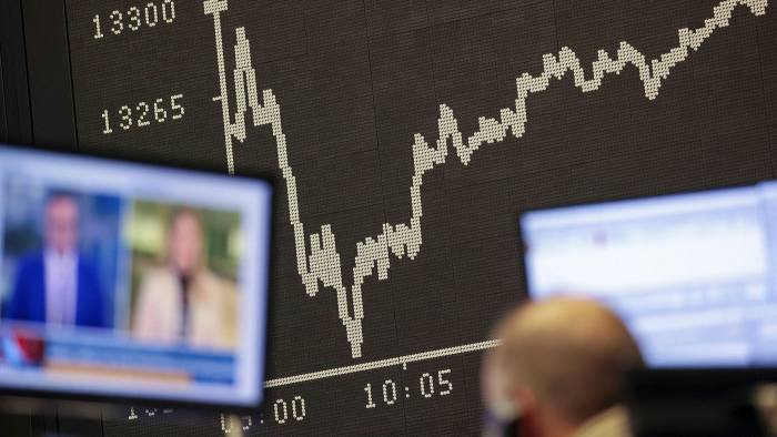 A trader watches news on a television monitor at the Frankfurt Stock Exchange