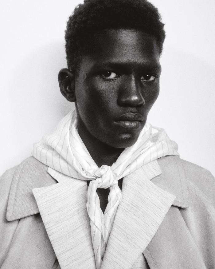 Moustapha wears Salvatore Ferragamo suedeMangiarotti Carrara overcoat, £6,520. Botter cotton blazer (seenunderneath), £985. Jil Sander by Lucie and Luke Meier rayon and cotton hoodedscarf, £140