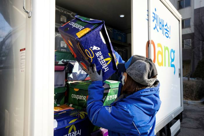 A Coupang employee unloads an eco-bag carrying fresh food from a delivery truck in Bucheon, South Korea,
