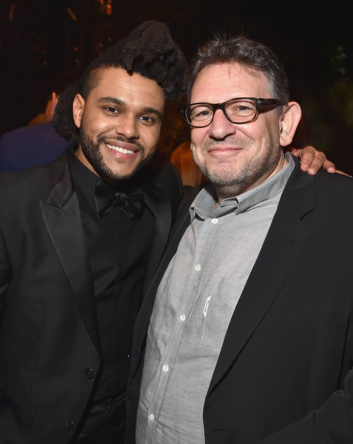 The artist named The Weeknd with his left arm around music executive Lucian Grainge