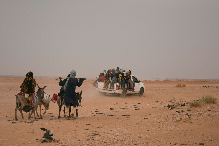 A pick-up truck carrying migrants passes close to Agadez in Niger. Traffickers have increasingly had to take more dangerous routes north