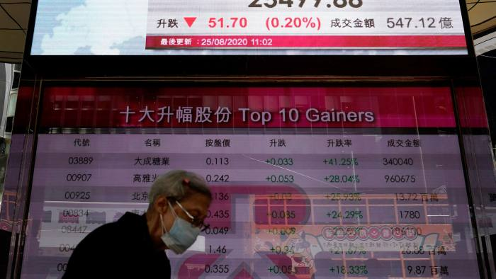 A woman wearing a face mask walks past a bank's electronic board showing the Hong Kong share index at the Hong Kong Stock Exchange on Tuesday