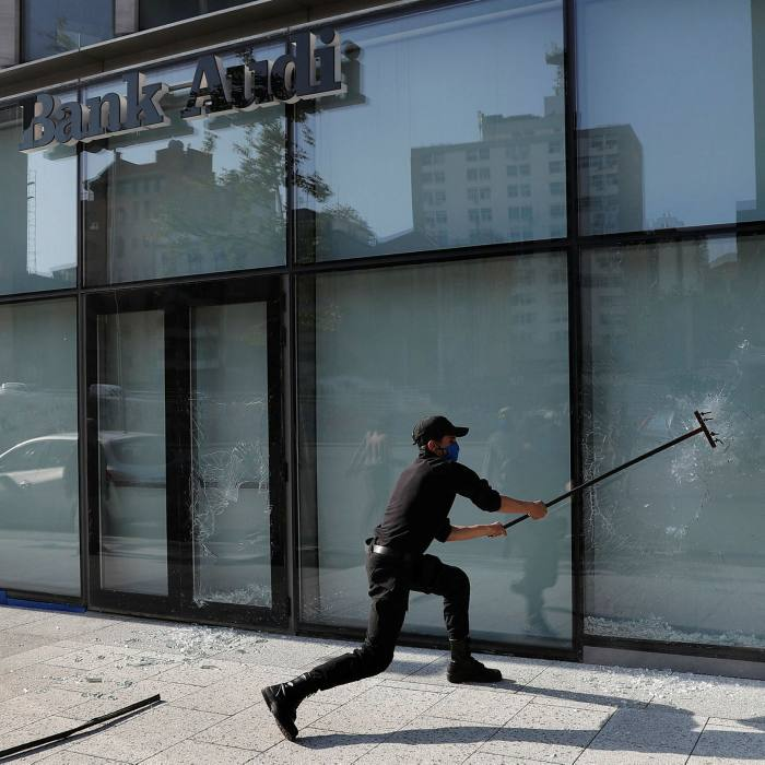 A protester smashes a bank window during demonstrations in Beirut in April