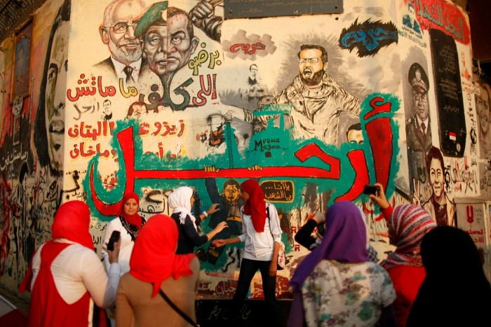 Women take pictures next to graffiti which reads 'Leave!' at Tahrir Square