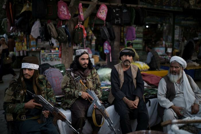 Taliban fighters sit next to street vendors at a market in Kabul on Friday