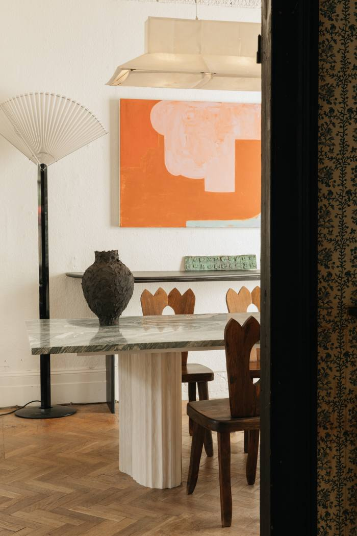 The dining room, with a table by EJR Barnes, ceramic vase by Noe Kuremoto, and Atelier LK Collection Tobia & Afra Scarpa lamp, Olavi Hanninen dining chair and artwork by Joseph Goody