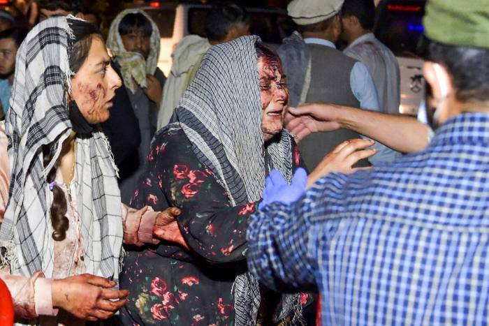 Wounded women arrive at a hospital for treatment after two bombings outside Kabul's airport on Thursday