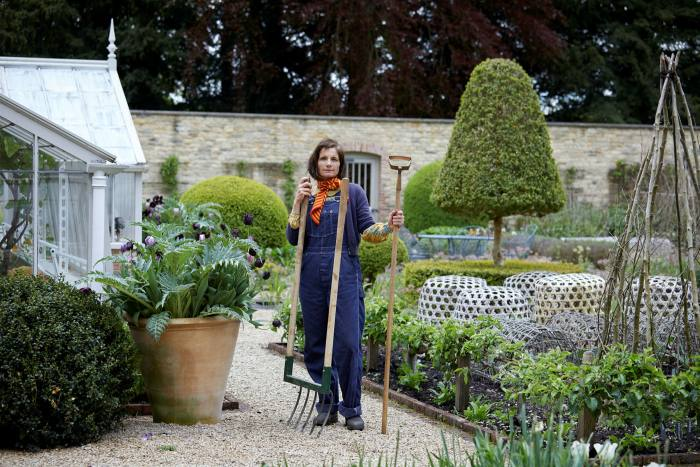 Gardner at Blackland House in Wiltshire.  She holds a wide fork and an oscillating bronze hoe