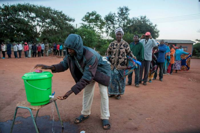People queue to wash their hands to prevent the spread of coronavirus before they vote in June in Lilongwe, Malawi