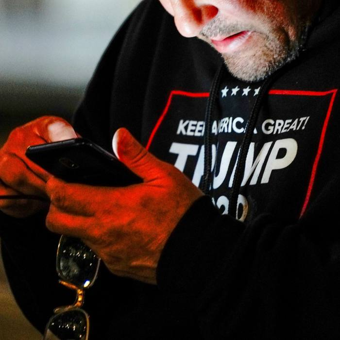 A Trump supporteruses his phone during a 'Stop the Steal' protest in Milwaukee