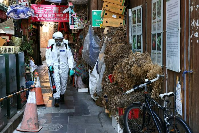 Workers disinfect Taipei's Wanhua district, an area that has one of the most Covid-19 cases in the city