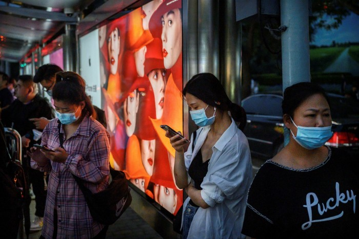 Chinese commuters on their mobile phones in Beijing. Products ranging from computer servers to the Apple iPhone could end up having two separate supply chains