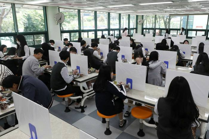 High school students eat a lunch at a school cafeteria which has screens on tables for preventing coronavirus infections