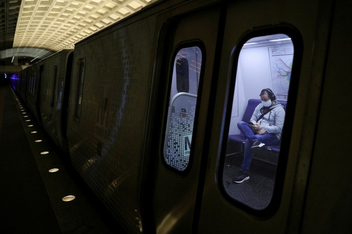 A lone passenger wearing a protective face mask sits on a Metro train in Washington. Concerns over coronavirus have spurred interest in car-sharing and subscription services