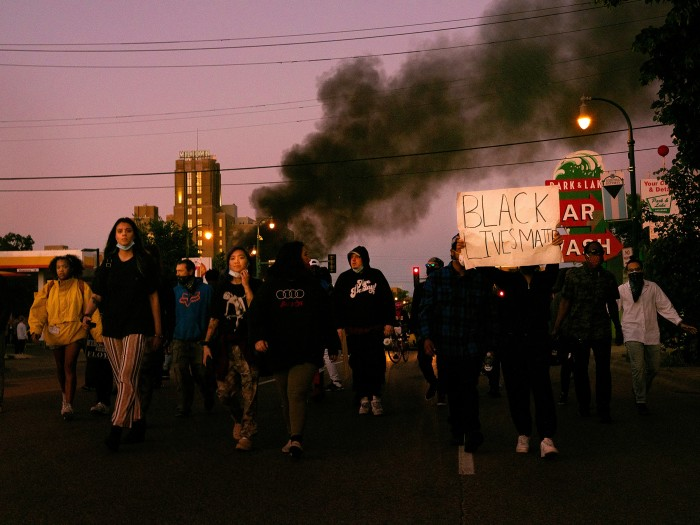 Protesters march in Minneapolis as smoke rises behind them
