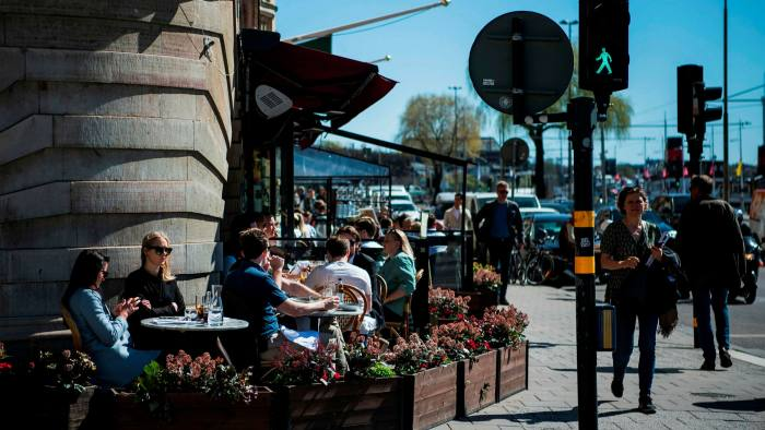 People have lunch at a restaurant in Stockholm during the coronavirus pandemic