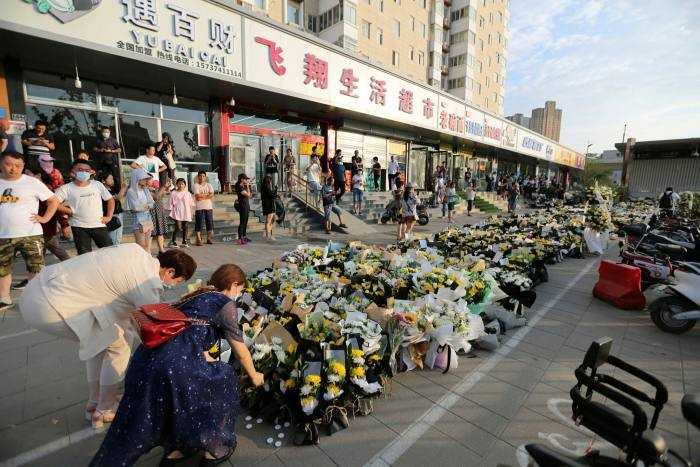 Residents place flowers outside a train station in Zhengzhou where at least 14 people died in a submerged railway carriage