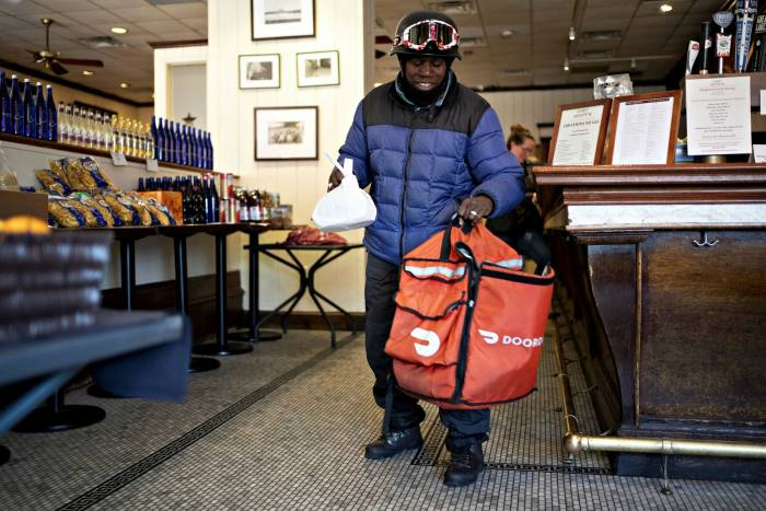 A DoorDash delivery worker places an order into a bag at Chef Geoff's restaurant in Washington