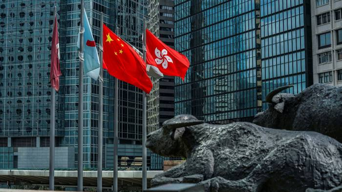 The flag of the Hong Kong Special Administrative Region, right, flies alongside the flag of China outside the Exchange Square complex