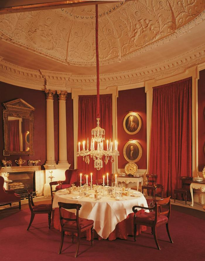 Claret-coloured walls in the dining room at Britwell House in Oxfordshire, designed by David Hicks
