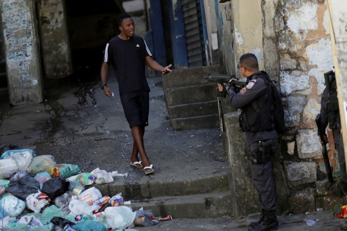 A police officer aims his gun at a man during a clash with residents of Morro do Borel favela. 'We have militarised police and armed drug traffickers and a scenario of urban war' in the slums, says Lucas Loubeck of Rio de Paz