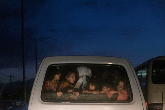 Children ride in the back of a vehicle near the Hamid Karzai International Airport in Kabul August 28