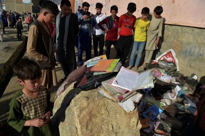 Onlookers stand next to the backpacks and books of victims following multiple blasts outside a girls' school in Dasht-e-Barchi on the outskirts of Kabul on May 9 2021