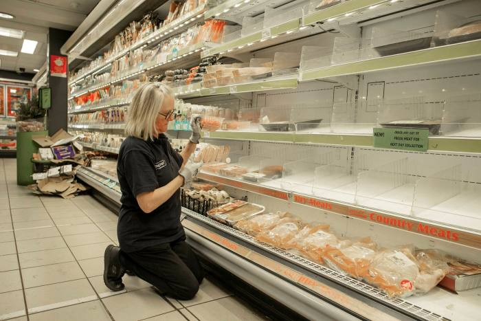 A female member of staff tidies empty shelves in a Nisa store