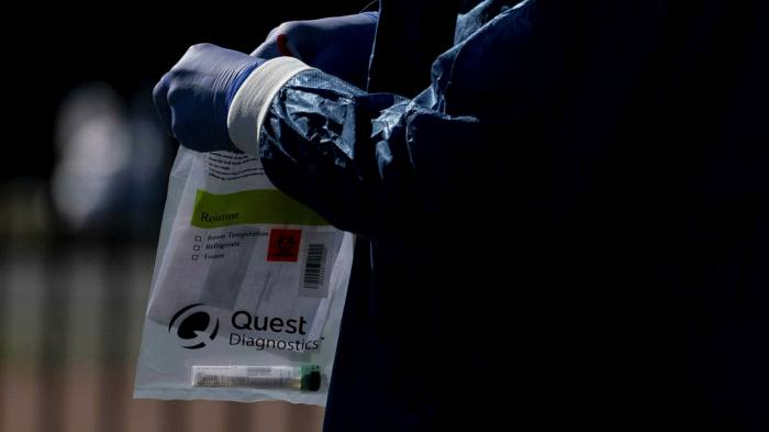 A healthcare worker holds a Quest Diagnostics bag containing a Covid-19 swab at a coronavirus drive-through testing site in Washington DC