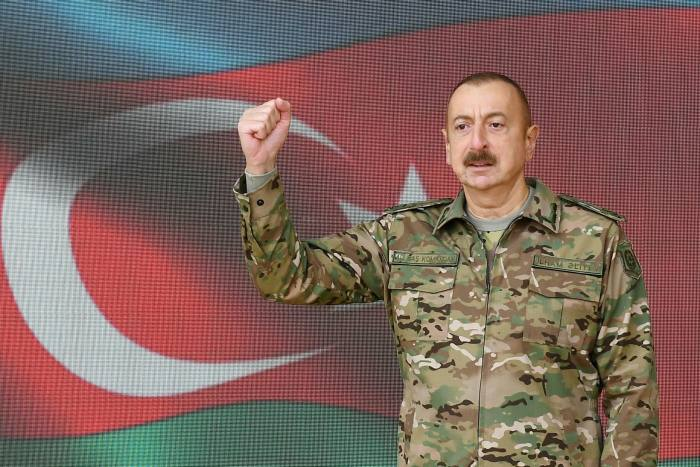 Azerbaijan's president Ilham Aliyev raises his fist during a televised address to the nation on Sunday announcing the capture of Shusha