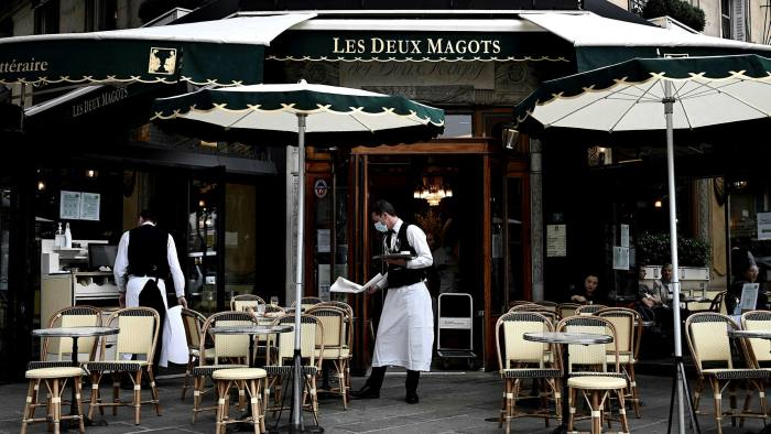 Waiters work at a café in Paris. The French purchasing managers' index for June rose more than economists had expected